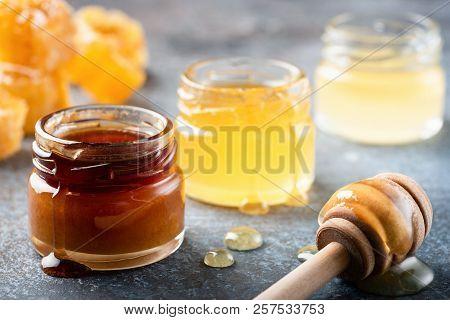 Honey In Jar With Wooden Honey Dipper, Liquid Honey. Closeup View