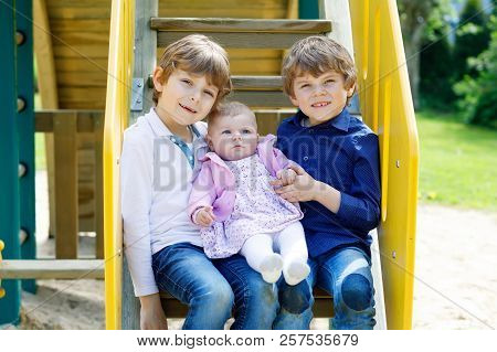 Two Little Happy Kid Boys With Newborn Baby Girl, Cute Sister. Siblings On Playground In Summer Or S