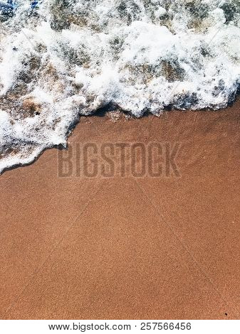 Wave Of The Sea On Sand Beach. The Wave Washes The Golden Sand. Foamy Waves Of The Sea Roll On The G