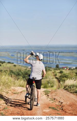 Cyclist. A Young Man On A Bicycle. Resting And Admiring The Scenery. Cyclist Drinking Water.