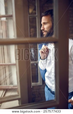 Male businessperson in office looking through open window