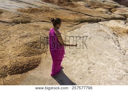 Woman In Ethnic Oriental Clothes Searches For Water In A Desert Area By The Method Of Dowsing