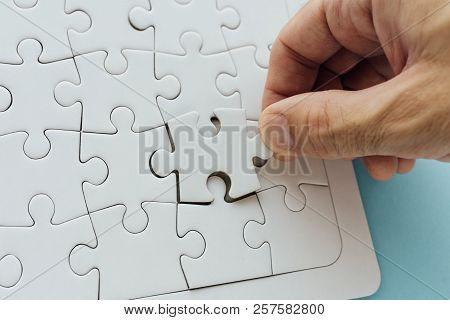 Missing Piece Of The Puzzle. Man Successfully Solving Jigsaw Puzzle, Hand Putting Last Element To Co