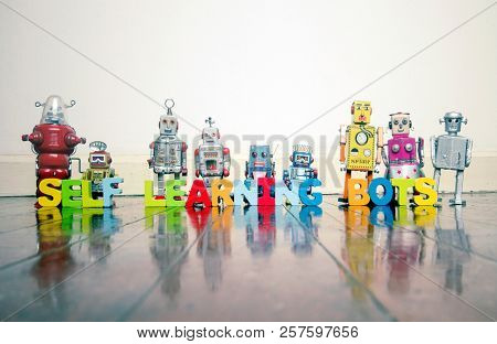 SELF LEARNING BOTS wooden letters and retro robot toys on a wooden floor with reflection