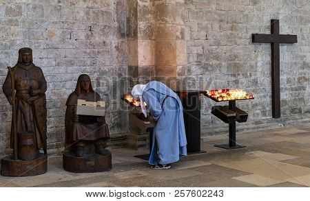 Vezelay, France - July 29, 2018: Church Interior With Nun Rearranging The Candles Of The Romanesque