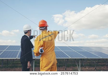 Clean Energy Concept.worker And Professional Manager Point At Solar Panels Background.engineer Wear