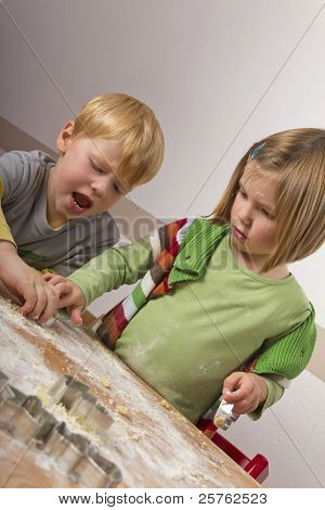 Two Kids Cutting Cookies For Christmas