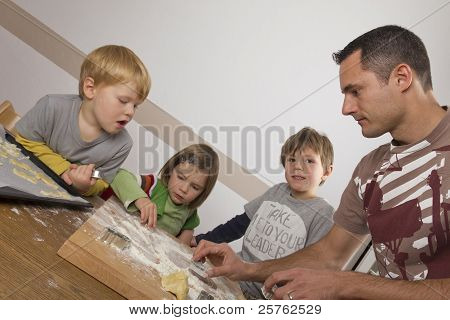 Father And His Kids Cutting  Cookies For Christmas
