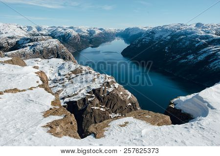 Top View Of The Pulpit Rock, Preikestolen. Scenic Landscape Of Fjord Between Rocky Shore And Mountai