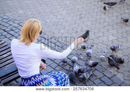 Girl Blonde Woman Relaxing City Square And Feeding Pigeons. Woman Tourist Or Citizen Toss Crumbs For