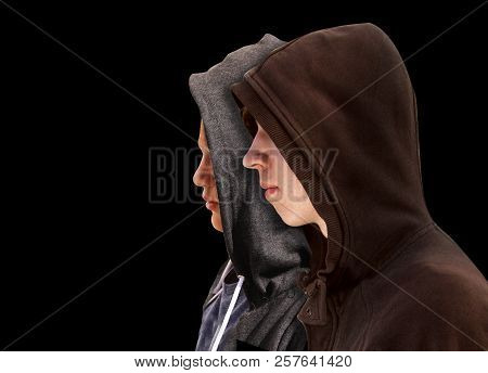 Two Troubled Teenage Boys With Black Hoodie Standing Next To Each Other In Profile Isolated On Black