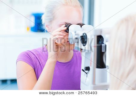 optometry concept - pretty, young female patient having her eyes examined by an eye doctor (color toned image; shallow DOF)