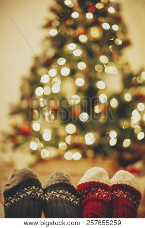 Stylish Festive Socks On Couple Legs On Background Of Golden Beautiful Christmas Tree With Lights In