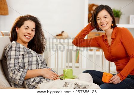 Expectant woman resting at home drinking tea with friend, looking at camera, smiling.