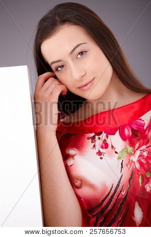 Beautiful young woman posing in red kimono, looking at camera, touching face, smiling.