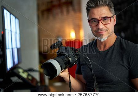 Older white man photographer in glasses at home holding photo camera, smiling,