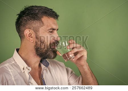 Life source and healthcare. Hangover and thirst. Health and dieting. Man with long beard hold water glass on green background. Hipster drink clean healthy water, refreshing. poster