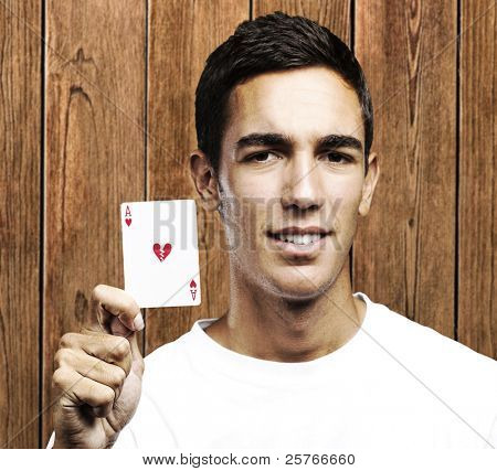 man holding poker card with broken heart symbol against a wooden wall