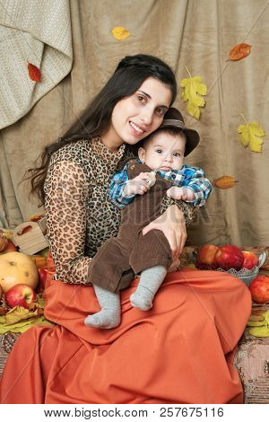 autumn concept - mother and child boy are on yellow leaves with fruits and vegatbles, red apples and pumpkins