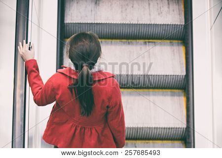 Woman commuter going to work walking up escalator stairs commuting in train station or airport.
