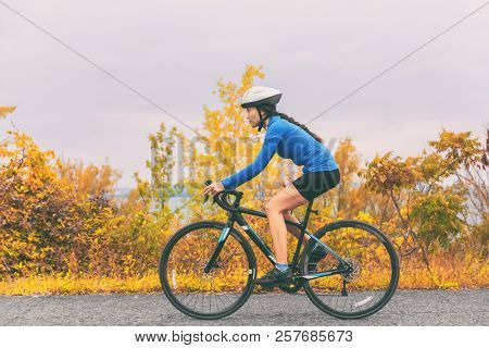 Bike cyclist outdoor woman biking road bicycle in autumn foliage nature.