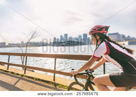 Urban biking girl riding road bike cycling in the city. Happy cyclist with downtown background by the St Lawrence river, Montreal, Canada.