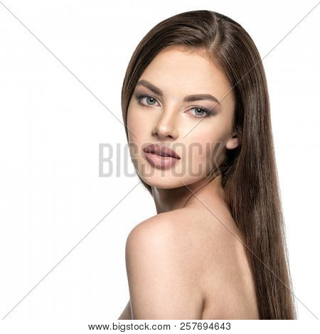 Face of the beautiful woman with long brown straight hair posing at studio