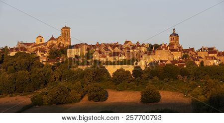 The UNESCO village of Vezelay on a hill with the Benedictine abbey and church of Saint Mary Magdalene at sunset in Yonne, France. poster