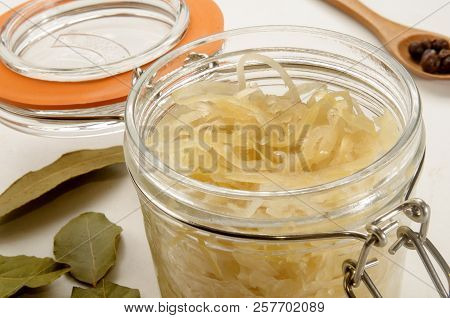Sauerkraut In A Glass Jar With Bayleaf And A Spoon With Juniper Berries