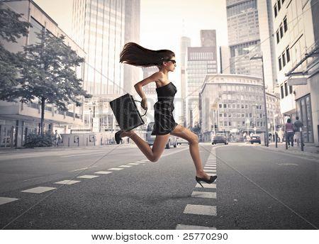 Beautiful elegant woman running on a city street
