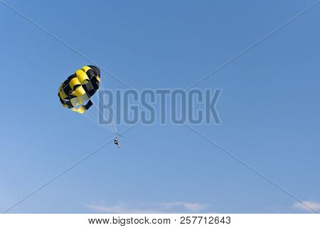 Parasailing. The Man Is Flying With A Yellow Parachute. Close-up