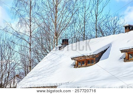 Roof Of A Low-rise Wooden Village House With Windows Under The Snow. Winter. Trees And Blue Sky With