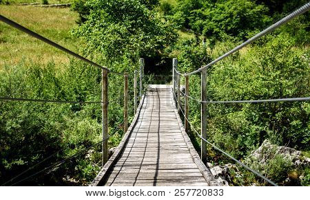 Wooden Hanging Bridge Leading Forward Over Green Mountain River.