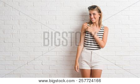 Young beautiful blonde woman over white brick wall cheerful with a smile of face pointing with hand and finger up to the side with happy and natural expression on face looking at the camera.