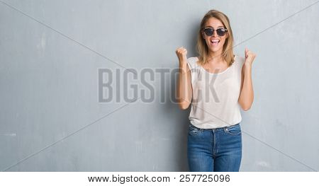 Beautiful young woman standing over grunge grey wall wearing fashion sunglasses screaming proud and celebrating victory and success very excited, cheering emotion