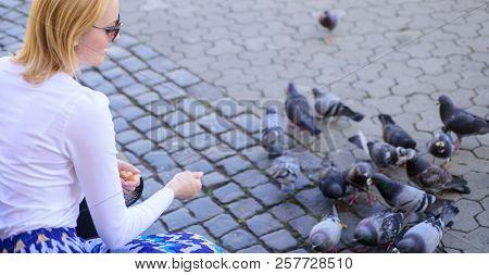 Group Doves On City Square Waiting Treats. Girl Feeding Dove Birds Urban Background. Girl Blonde Wom