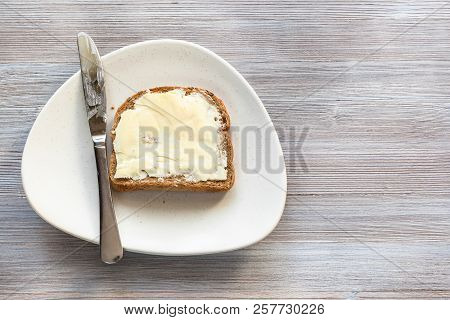 Top View Of Bread Sandwich With Buttered Butter And Steel Knife On White Plate On Gray Wooden Board