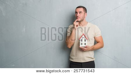 Young caucasian real state agent man over grey grunge wall holding house serious face thinking about question, very confused idea
