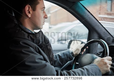 Man seats on driver seat at steering wheel in modern car on winter day, profile view.