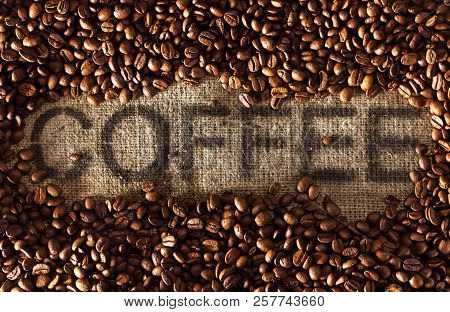 Heap Of Roasted Coffee Beans On Burlap Background