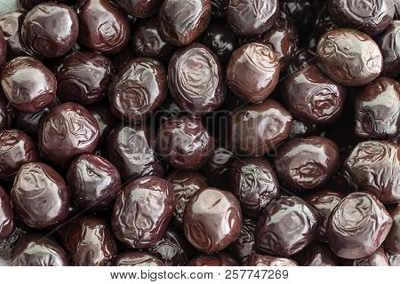 Background Texture Of Cured Grade A Black Olives From The Mediterranean In A Close Up Full Frame Vie