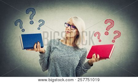 Confused Young Student Girl Holding Two Different Books Has To Choose Between Red And Blue. Doubt An