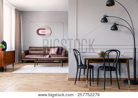 Real Photo Of Metal Lamp Standing Next To Dining Table With Two Black Chairs In Open Space Flat Inte