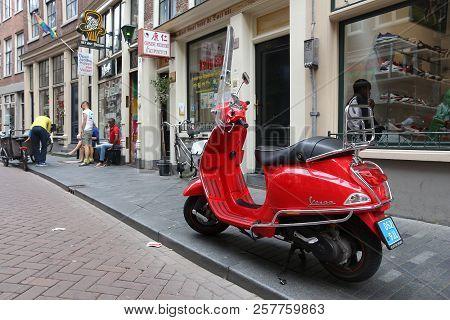 Amsterdam, Netherlands - July 8, 2017: Red Piaggio Vespa Scooter Parked In Amsterdam, Netherlands. V