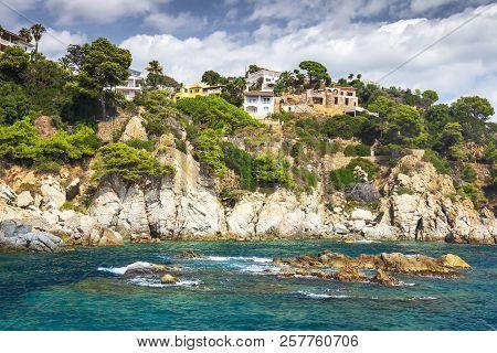 Rocky Coastline In Mediterranean In Lloret De Mar, Costa Brava, Spain With Village Houses On Hills A