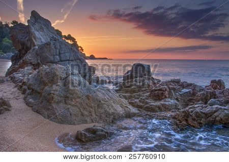 Amazing Seascape With Rocks And Stones On Beach At Sunrise. Beautiful Colorful Sky At Dawn Over Idyl