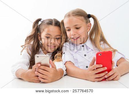 Online Life Concept. Schoolgirls Cute Pupils Use Smartphones Big Diagonal Screen To Check Social Net
