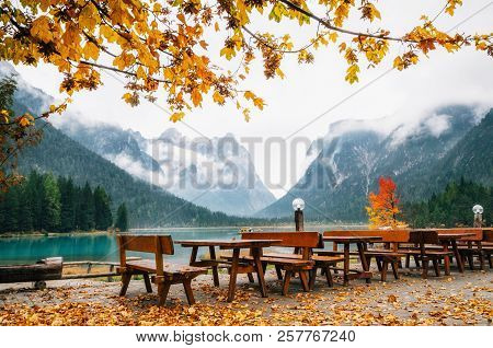 Dobbiaco Lake Or Toblacher In Dolomites With Wooden Tables And Benches In Outdoor Cafe Restaurant In