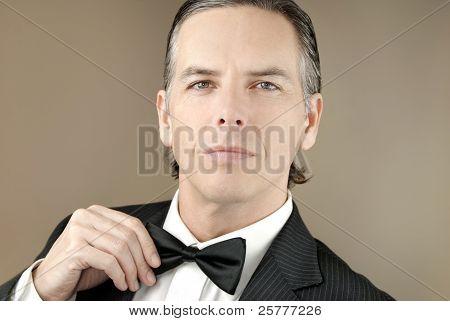 Confident Gentleman In Tux Adjusts Bowtie