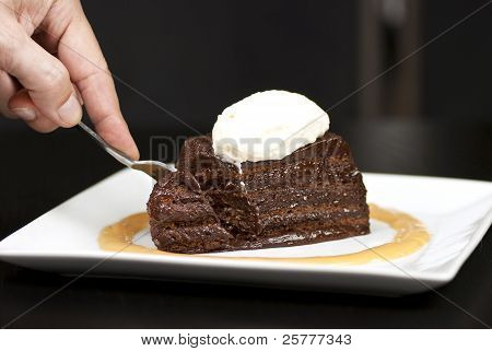Hand Holding Fork Slicing Into A Chocolate Marquise With White Chocolate Marscapone And Butterscotch